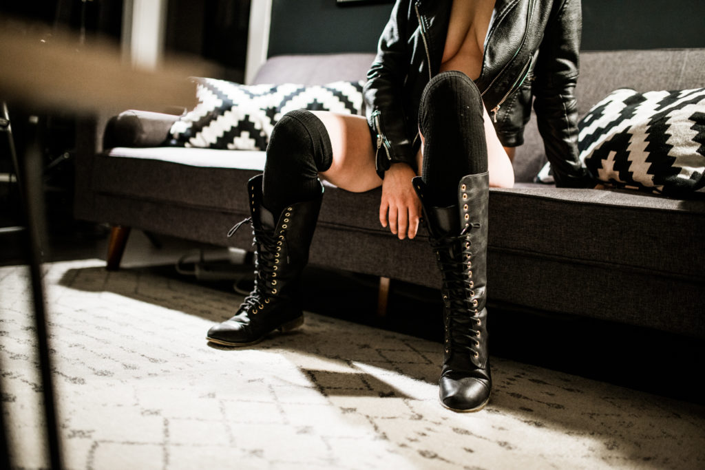 horizontal portrait of a woman in black leather jacket and boots. a boudoir portrait where her face isn't visible.
